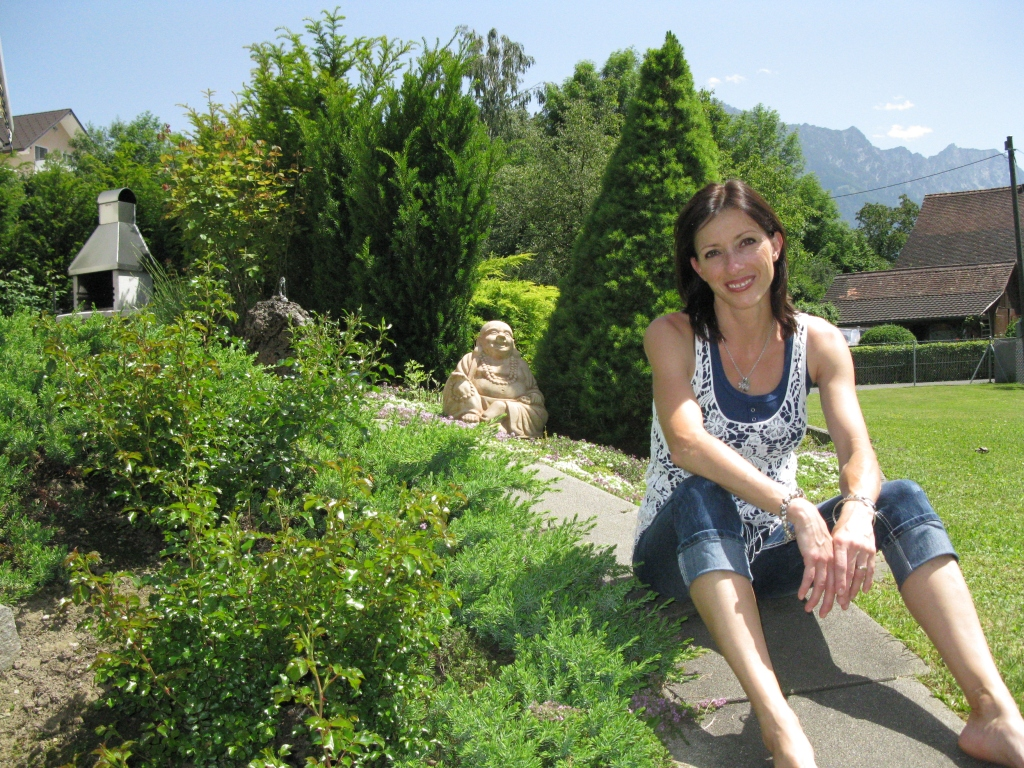 Erika sitting in her garden.